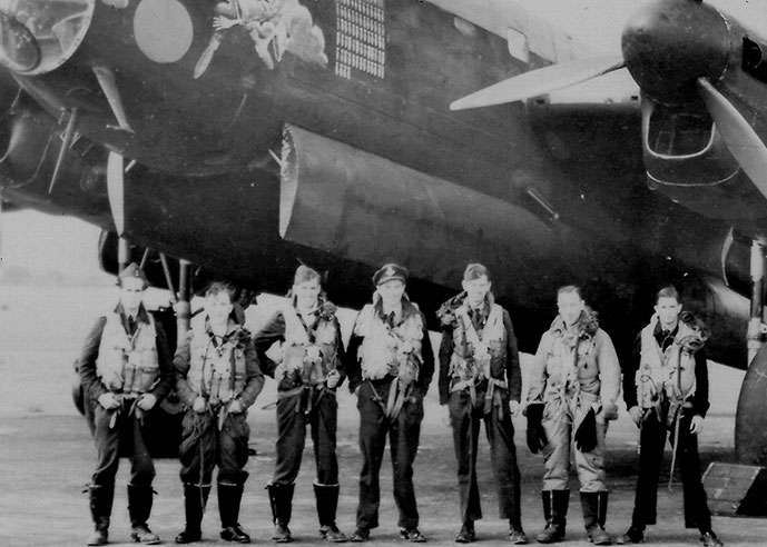 Air crew standing in front of a Second World War aircraft